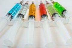 Seringas médicas plásticas que contêm soluções multicoloridos com fundo branco Imagens de Stock