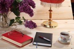 Seringen, boek, notitieboekje, bril, kop thee en schemerlamp Stock Foto