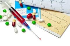Seringue, électrocardiogramme et tablettes Image stock