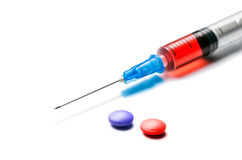 Seringue avec le liquide rouge et pilules sur le blanc Photo libre de droits