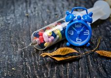 Seringue avec les pilules et l'horloge Photo stock