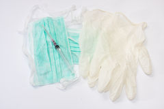 Seringue et aiguille sur le masque chirurgical et les gants Image stock