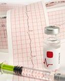 Seringue et fiole sur l'électrocardiographe Photographie stock
