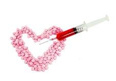Seringue et forme rose de coeur de forme de pillules image libre de droits