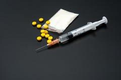 Seringue et paquet jetables de poudre et de pilules blanches sur le noir Photographie stock libre de droits