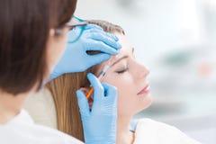 Seringue faciale de traitement de station thermale de remplisseurs de femme de Botox jeune photos libres de droits