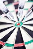 Seringues coincées dans un dartboard Photographie stock libre de droits