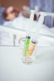 Seringues dans une tasse de mesure en verre avec le mensonge brouillé de garçon de maladie Image libre de droits