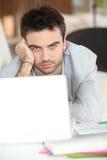 Serio-sguardo del tirante con il computer portatile Immagini Stock Libere da Diritti