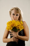 Serious. There is women with yellow flowers looks at you royalty free stock photography