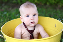 Serious 7-month-old white baby in yellow bucket Stock Image