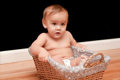 Serious 9 month old baby in basket Royalty Free Stock Image