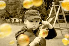 Serious. Boy, during blowing soap bubbles. Image in sepia, hand tinted to give a dreamy effect Royalty Free Stock Images