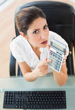 Serious accountant holding a calculator looking at camera Royalty Free Stock Photography