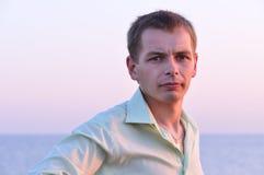 Serious adult man. At sunrise near the sea Stock Image