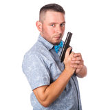 Serious adult man with a beard in a blue bow tie in summer shirt with a firearm in the hands Royalty Free Stock Photography