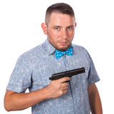 Serious adult man with a beard in a blue bow tie in summer shirt with a firearm in the hands of the hands on an isolated white bac Royalty Free Stock Photos