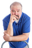 Serious Adult Man Leaning Against the Chair. Close up Thoughtful Adult Bearded Man Leaning Against the Back of a Chair with Hand on his Face and Looking at the Royalty Free Stock Photography