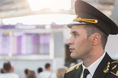 Assured handsome airman in airport. Serious adult pilot wearing cap is looking aside with self-confidence. Profile. Copy space on left side Royalty Free Stock Image
