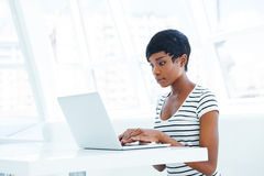 Serious african american businesswoman sitting with laptop at the table Royalty Free Stock Photography