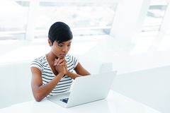 Serious african american businesswoman sitting with laptop at the table Royalty Free Stock Photos