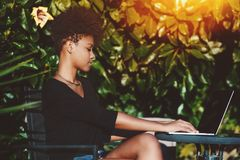Biracial female with net-book in a garden royalty free stock photography