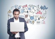 Serious African American man laptop, business plan Stock Images