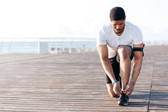 Serious african american young sportsman laces his sneakers Stock Photos