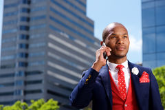 Serious african businessman talking on mobile phone in the city Stock Photo