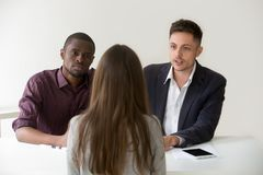 Serious african and caucasian hr managers interviewing female jo. B applicant, diverse recruiters listening to candidate answering question at hiring Royalty Free Stock Images