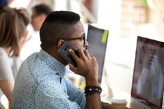 Free Serious African Employee Talking On Phone Consulting Client In Office Royalty Free Stock Photos - 138893638
