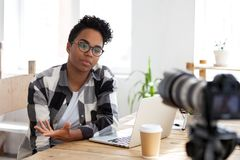 Serious african girl youtuber blogger talking to camera shooting video. Serious african girl youtuber blogger vlogger talking to camera shooting educational royalty free stock image