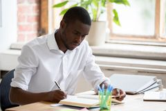 Serious african man university student studying reading textbook making notes stock photo