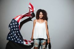 Serious african woman standing and waving with american flag. Isolated over gray background Stock Images