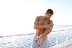Serious african young sportsman using smartphone at the sea pier stock photos