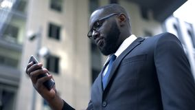Serious afro-american businessman working on smartphone, business application royalty free stock photos