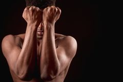 Serious Afro man does not want to show his weakness. Serious naked Afro man does not want to show his weakness. closing his face with arms. male sob.heavy defeat Royalty Free Stock Images