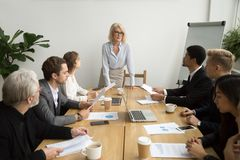 Serious aged businesswoman leading corporate team meeting talkin. G to multiracial employees, senior female boss ceo leader discussing work with diverse stock photo