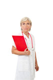 Serious aged doctor with clipboard Stock Photo