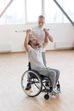Serious aged general practitioner teaching the disabled in the gym Royalty Free Stock Photography