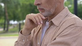 Serious aged man with hand on chin planning purchase, health problem, choice stock video footage