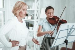 Serious aged woman looking at the note charts. Professional musician. Serious aged women looking at the note charts while conducting a music lesson stock photos