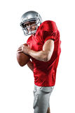 Serious American football player in red jersey holding ball. On white background Stock Photos