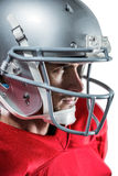 Serious American football player in red jersey looking away. Close-up of serious American football player in red jersey looking away against white background Stock Images