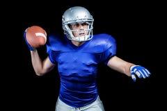 Serious American football player throwing ball Stock Photos