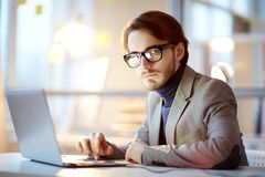 Serious analyst. Serious broker in elegant suit and eyeglasses witting by workplace in front of laptop display and analyzing online information stock photography