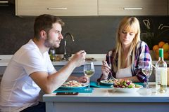 Free Serious And Unhappy Young Couple Eating Quinoa Salad In The Kitchen At Home. Royalty Free Stock Images - 124072819