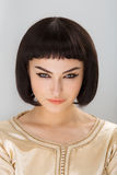 Serious andgy girl with Cleopatra's make-up and haircut posing in studio Stock Photos