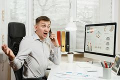 Serious and engrossed business man in shirt sitting at the desk, working at computer with modern monitor. Manager or worker. Serious angry stress business man stock photos