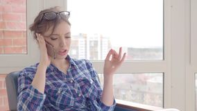 Serious and angry woman talking on the mobile phone at home. Serious and angry woman talking on the mobile phone at home stock video footage